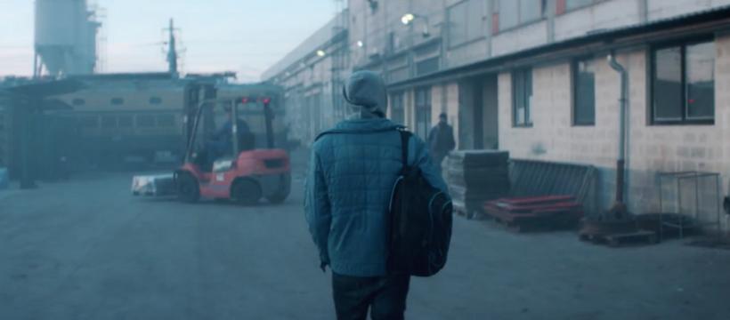 adolescent devant une usine