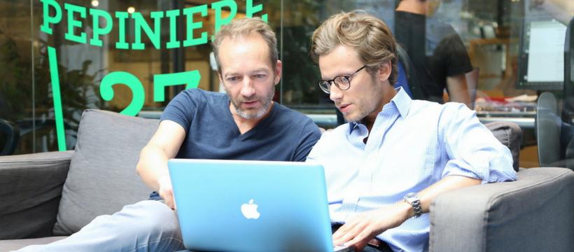 deux hommes travaillent sur un mac