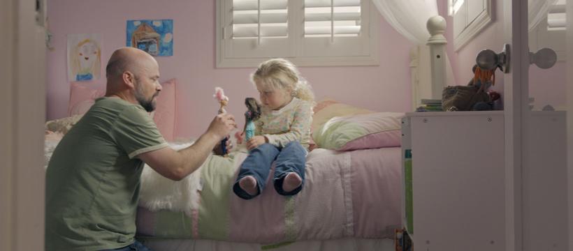 un père et sa fille jouent à la poupée