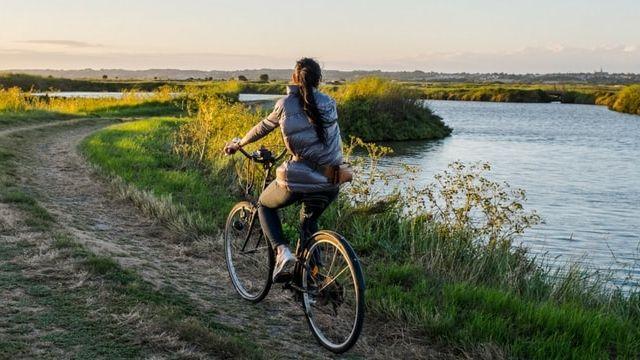Jeune femme à vélo sur une route de campagne