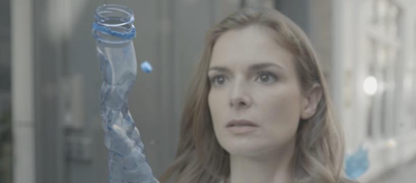 femme face à une bouteille plastique
