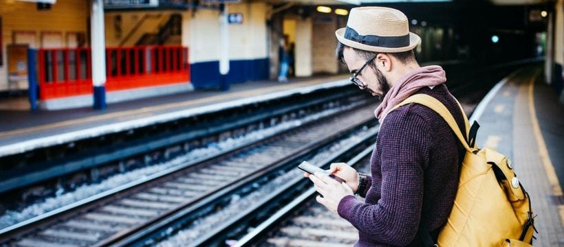 Un homme attend sur le quai d'une gare smartphone à la main