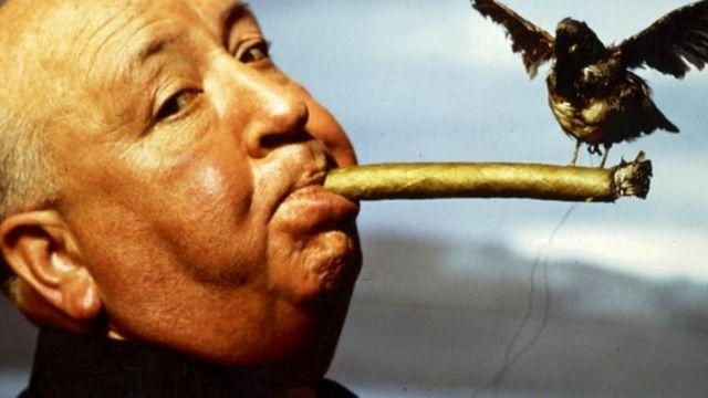 Alfred Hitchcock en train de fumer avec un oiseau