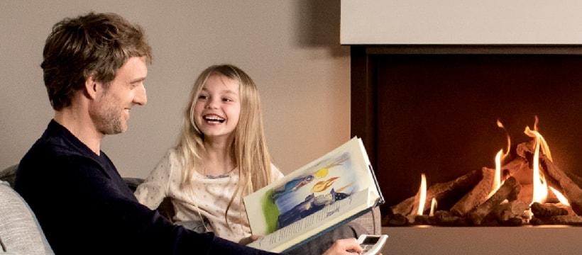 un pere et sa fille rient par ce quils ont la flamme instantanee dans le cheminee