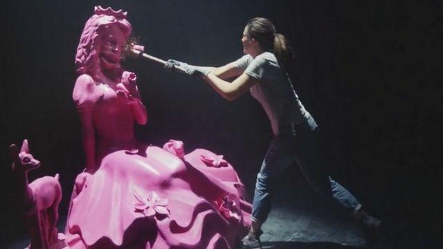 femme detruisant une statue de femme clichee