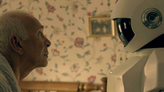 Un vieil homme et un robot se regardent