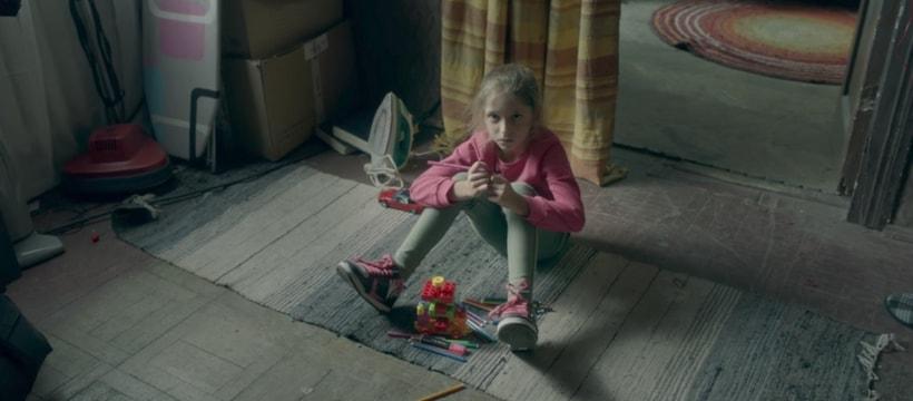 enfant assise dans une maison insalubre