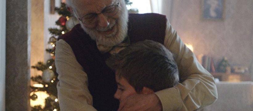 Un grand-père prenant son petit-fils dans ses bras pour SOS Amitié