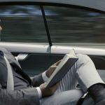un homme lit dans une voiture autonome
