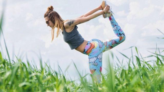 femme qui fait du yoga dans un champ