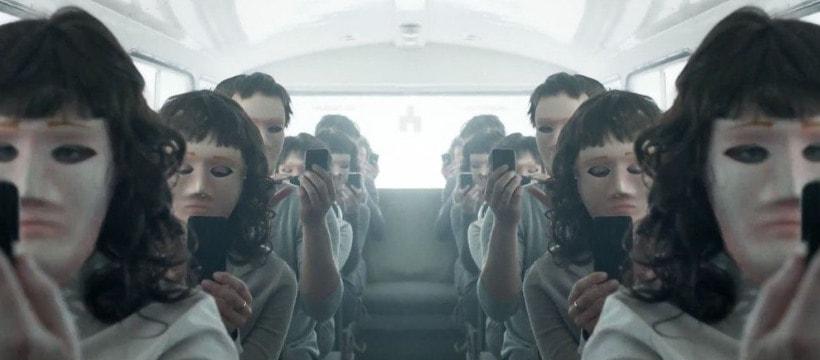 gens assis dans un bus aveec leur smartphone et des masques