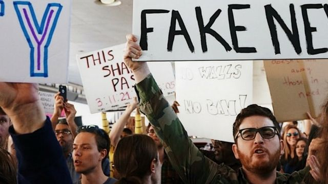 homme tenant une pancarte fake news dans une manifestation