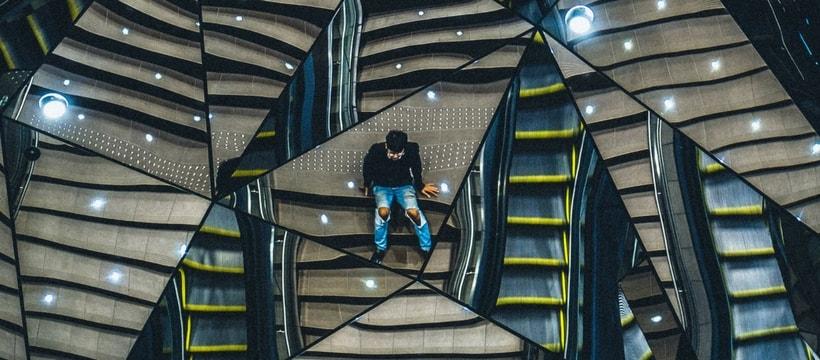 un homme assis sur des escaliers, se reflétant dans plusieurs miroirs