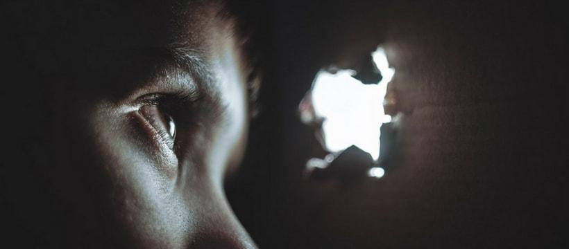 Un oeil d'enfant qui regarde dans le trou d'un mur