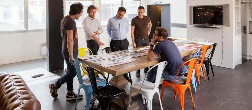 quatre personnes qui discutent autour dune table