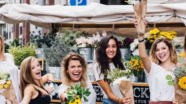 Des femmes heureuses agitent des fleurs