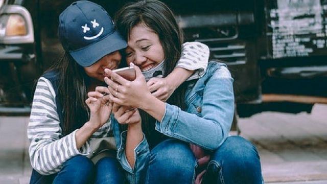 deux amies rient ensemble devant leur smartphone