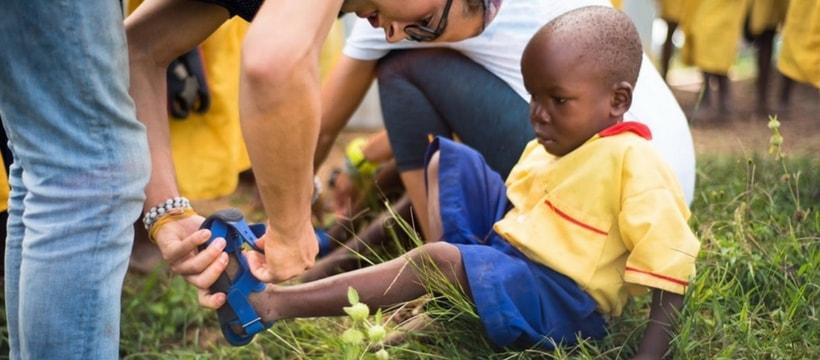 Un enfant noir en train d'essayer une chaussure