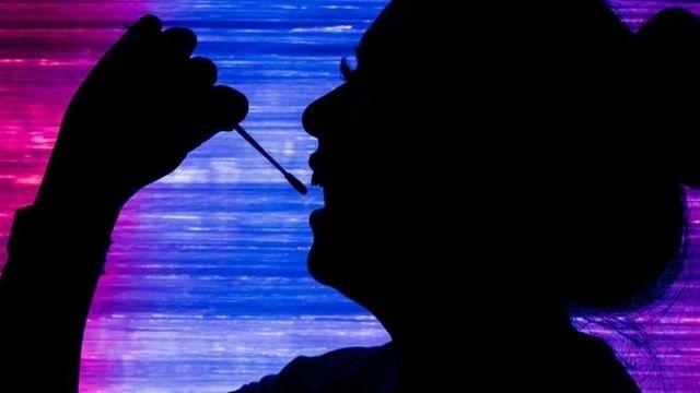 une femme en train de prélever son ADN avec un coton tige