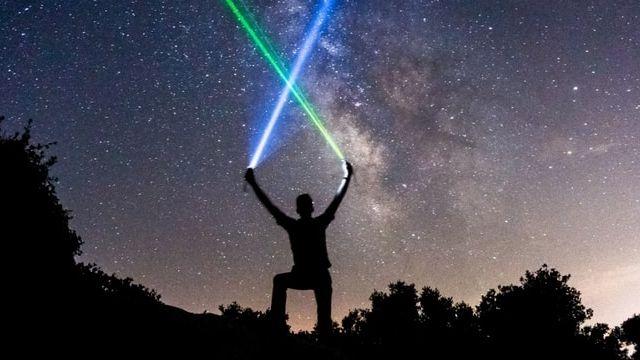 Un homme en train de brandir des lasers sur un ciel étoilé