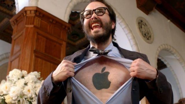 un homme avec le torse tatoué d'un logo Apple