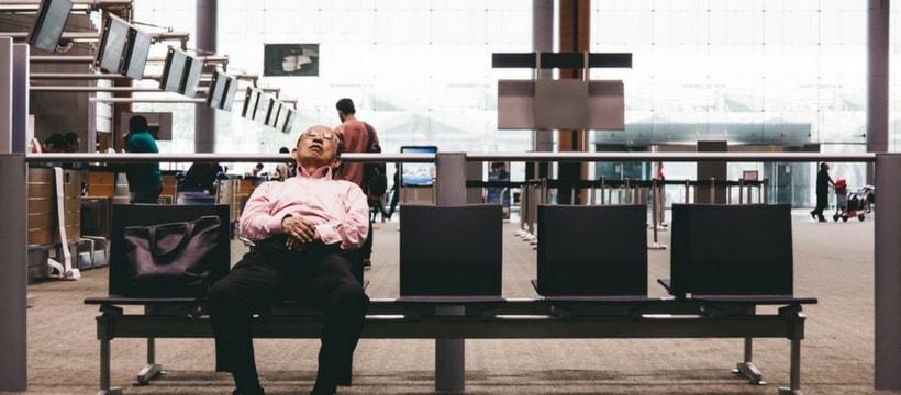 une personne dort en attendant son vol