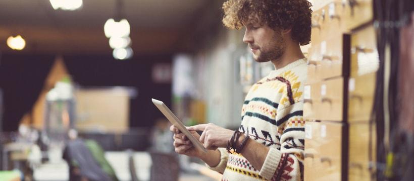 Un homme au milieu de cartons en train d'utiliser une tablette