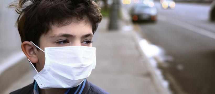 enfant avec un masque respiratoire dans la rue