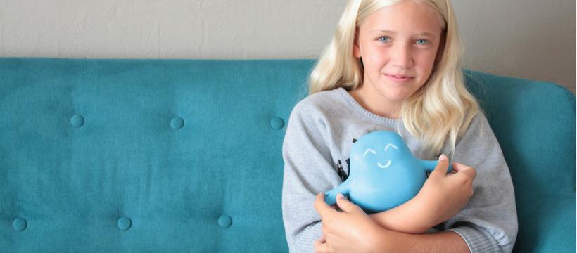 petite fille blonde assise sur un canapé bleu