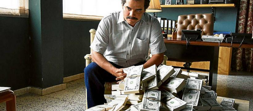 Une scène de Narcos, où Pablo Escobar est assis devant une pile de billets