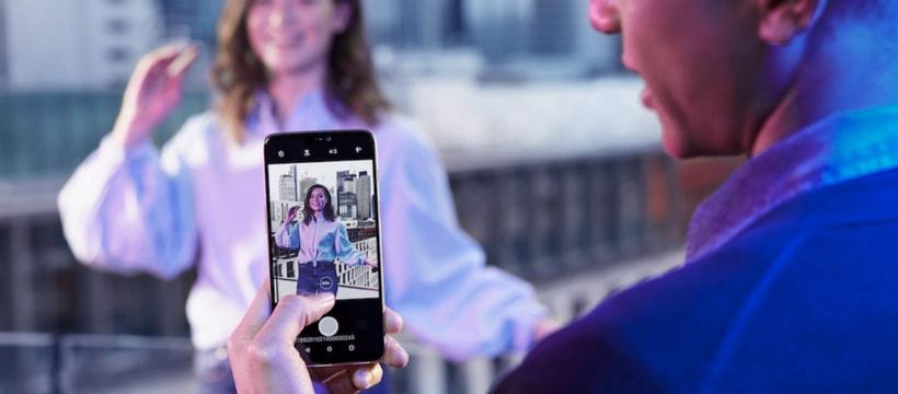 Un homme en train de prendre une femme en photo avec le OnePlus 6