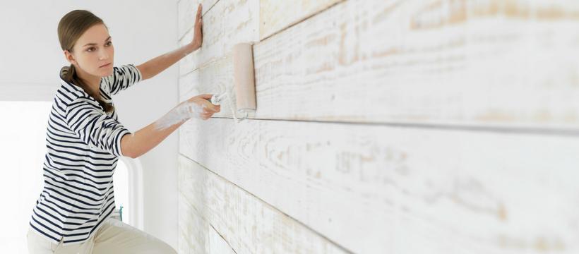 une femme qui peint une maison