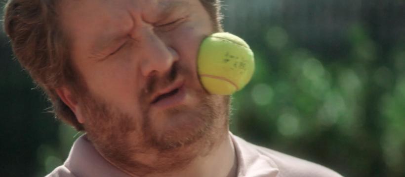 homme qui reçoit une balle de tennis sur le visage