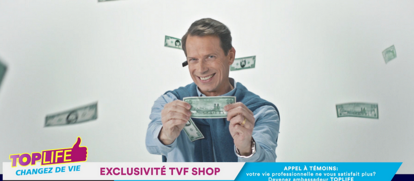 un homme qui tient un billet à la télévision
