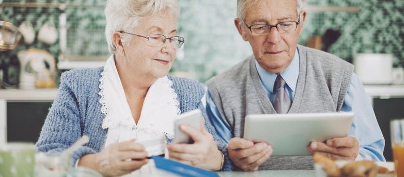 Deux seniors, un homme et une femme, en train de tenir une carte bancaire, un téléphone et une tablette