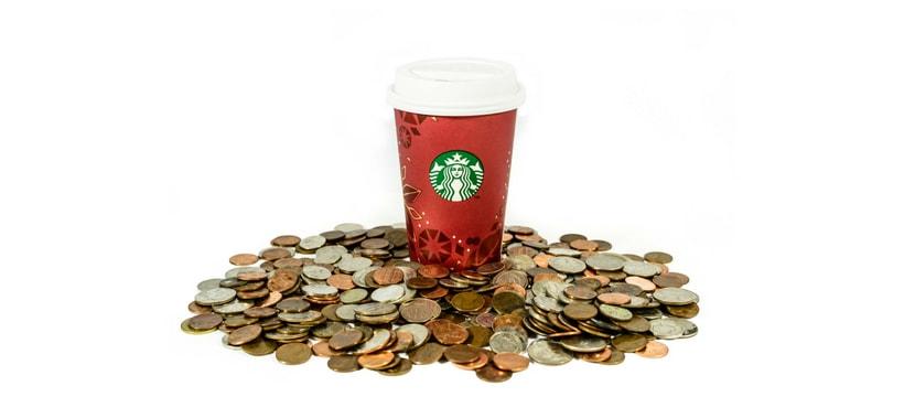 Un gobelet Starbucks posé sur des pièces de monnaie