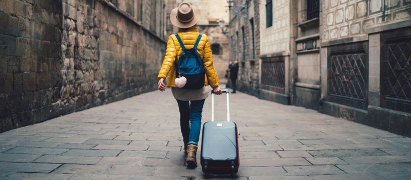 une femme de dos qui part en vacances avec sa valise