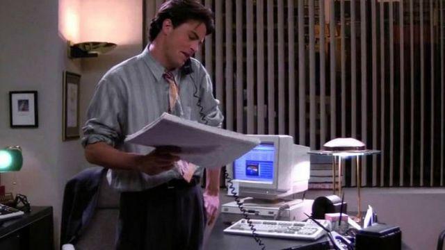 Chandler Bing au téléphone, dans son bureau, dans la série Friends