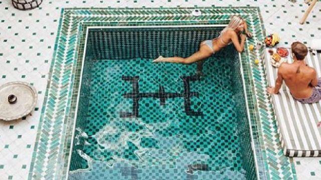 Une femme dans une piscine, et son compagnon, au riad Yasmine à Marrakech