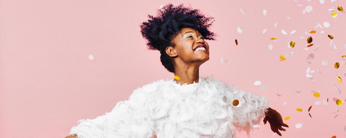 Une femme souriante lance des confettis