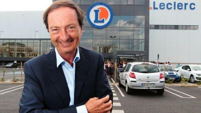 Michel Edouard Leclerc posant devant un magasin Leclerc, avec le sourire