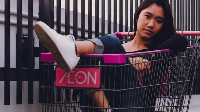 femme dans un chariot de supermarché