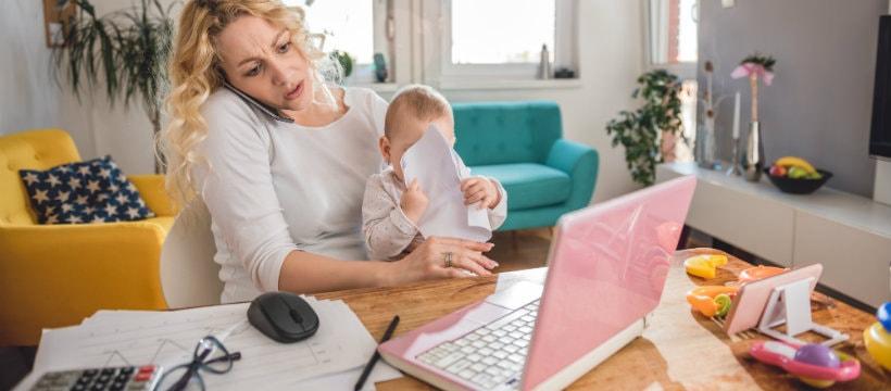 Une jeune mère en train de travailler avec son enfant dans les bras