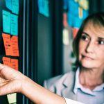 salariés devant un tableau de post-it travaillant en méthode agile