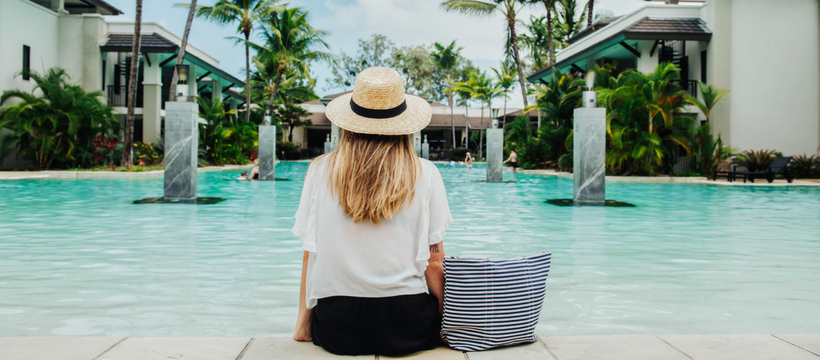 Une femme blonde assise de dos au bord d'une piscine