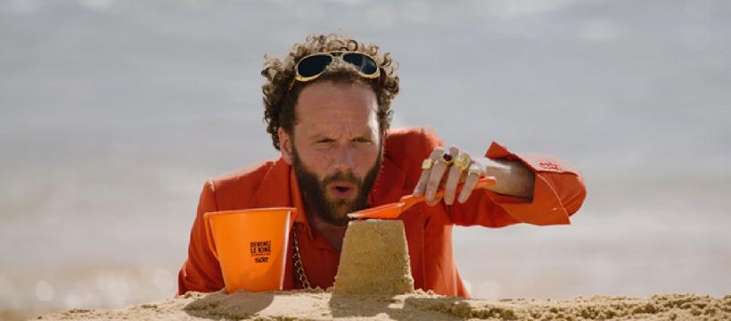 un homme qui fait un château de sable à la plage