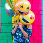 Une femme avec des ballons en forme d'emoji