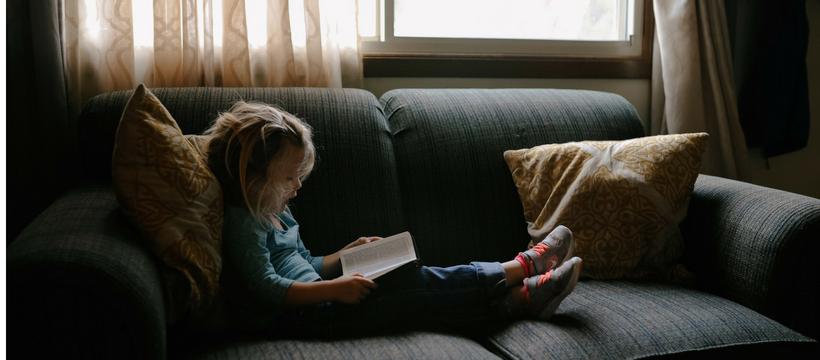 petite fille blonde qui lit un livre sur un canapé