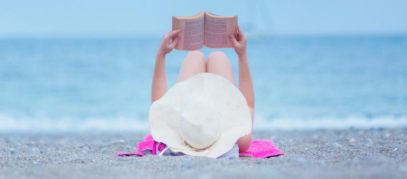 Une femme allongée sur la plage en train de lire un livre