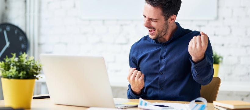 Un jeune homme en train de se réjouir derrière son ordinateur portable